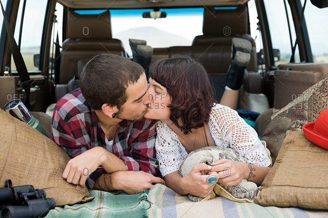 Young couple kissing in back of suv