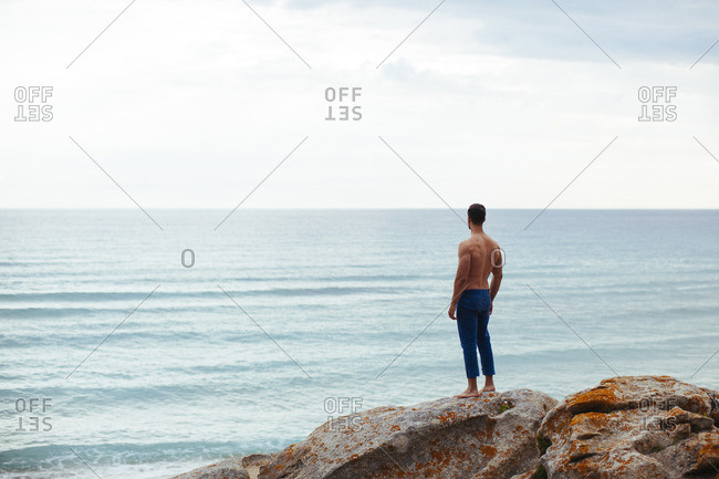 Shirtless man standing on rock overlooking sea