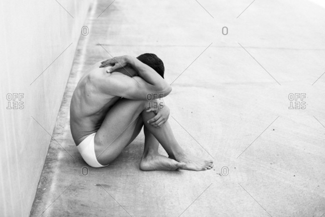 Muscular man sitting against cement wall