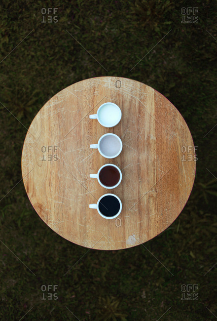 Overhead view of four mugs of hot beverages on table
