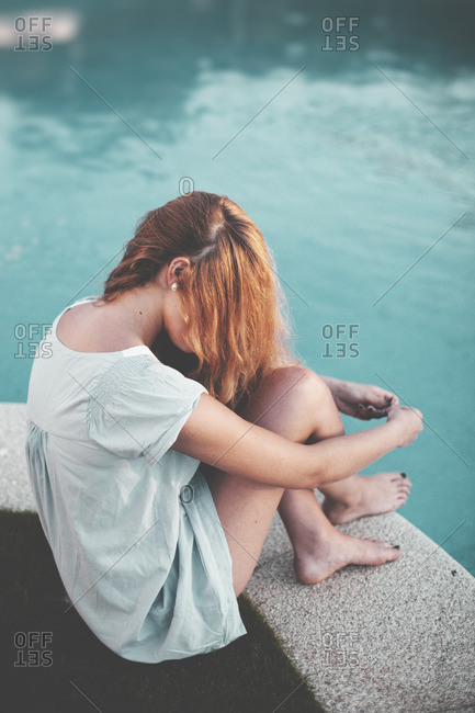 Woman sitting on edge of pool with hair covering face