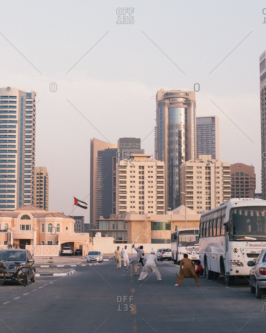 Dubai, United Arab Emirates  - October 14, 2015: Men roughhousing in a street below skyscrapers