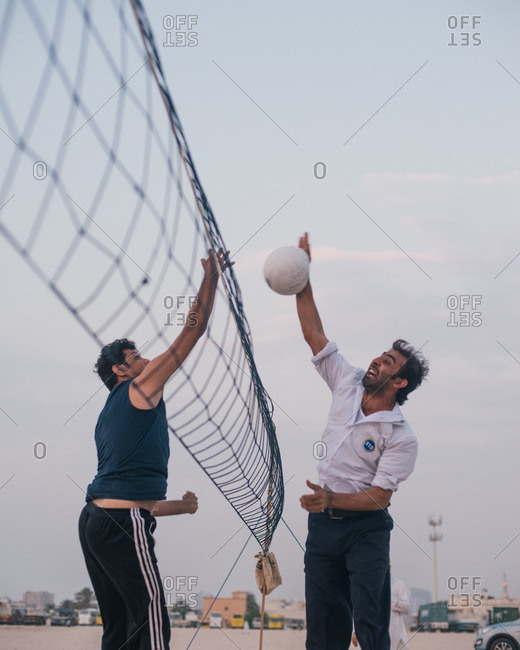 Dubai, United Arab Emirates  - October 14, 2015: Two men playing volleyball at a net