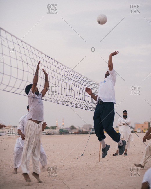 Dubai, United Arab Emirates  - October 14, 2015: Friends playing a game of volleyball