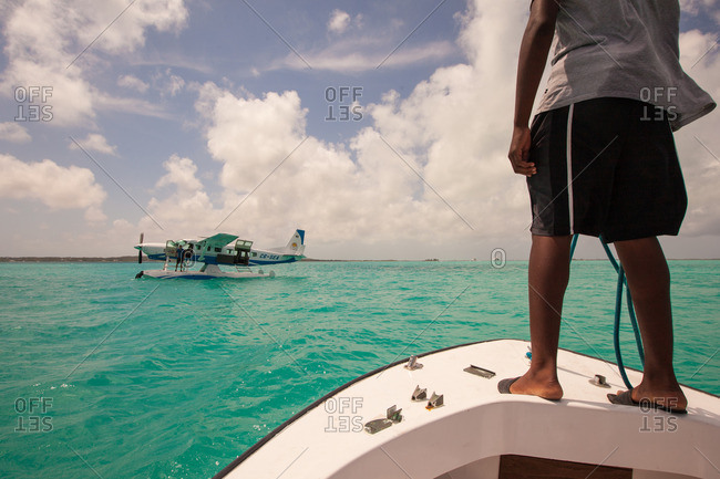 Bahamas - August 25, 2016: Man standing on the bow of a boat in facing a seaplane