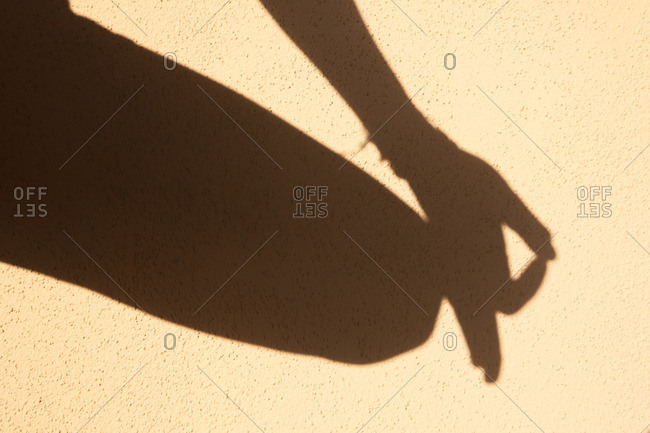 Shadow of a hand resting on a knee in a mudra position
