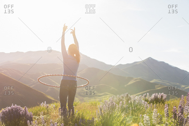 Woman on a mountainside twirling a hula hoop around her waist