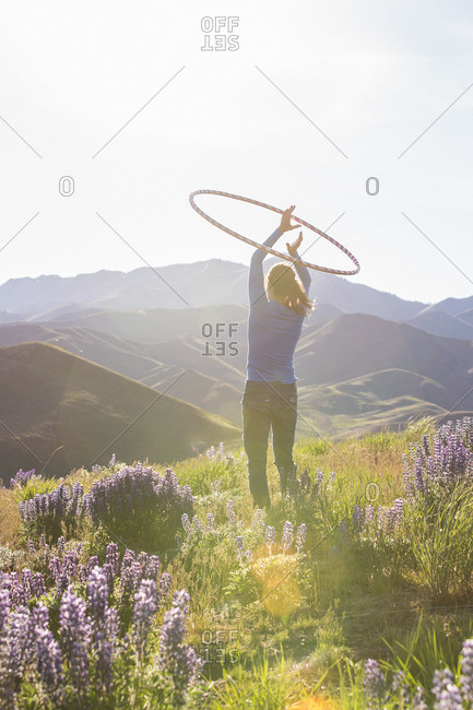 Woman on a mountainside playing with a hula hoop