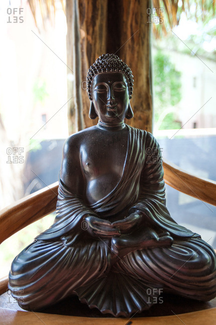 Buddha statue on a wooden outdoor surface