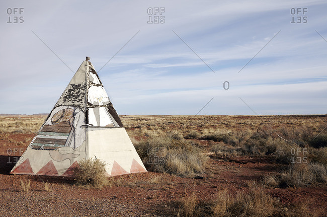 Teepee with peeling paint and canvas in a desert