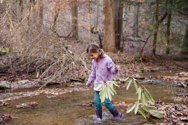 Girl holding a branch walking through a creek