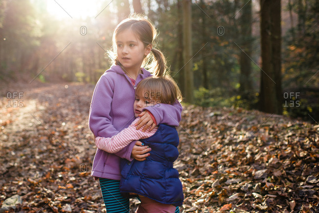 Two sisters hugging on a trail in a forest