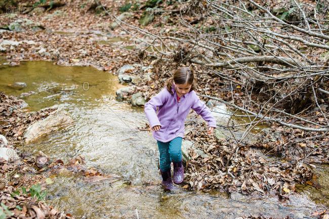 Girl splashing through a stream in the woods