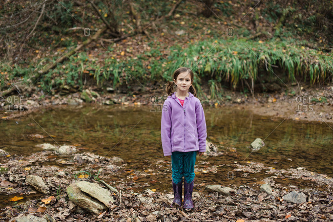 Girl standing in a stream in a forest