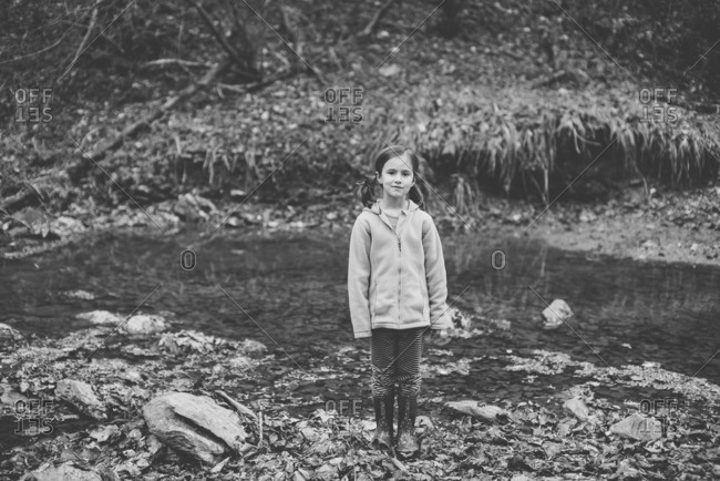 Girl standing in a creek in the middle of a forest