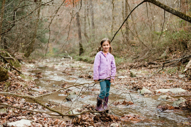 Girl standing in a stream in the woods in autumn
