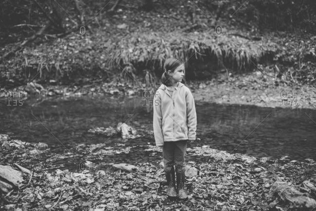 Girl standing on leaves in a creek in the forest