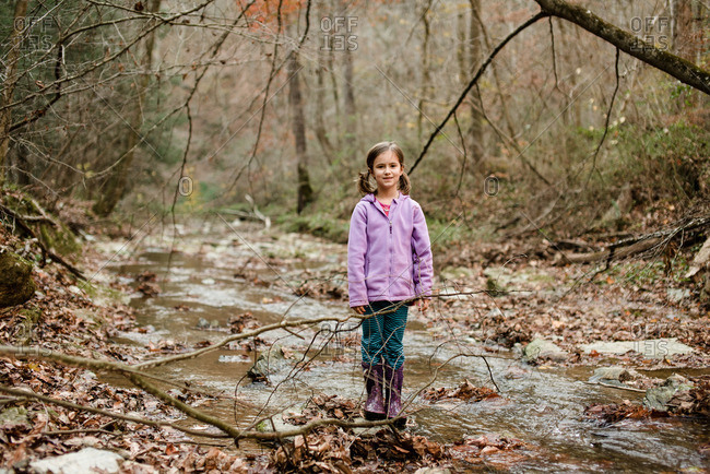 Girl standing in a stream in an autumn forest smiling