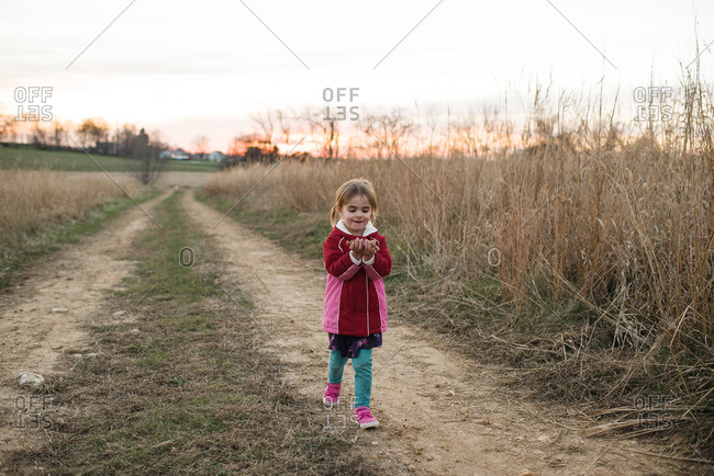 Little girl walking on a farm path with leaves in her hands
