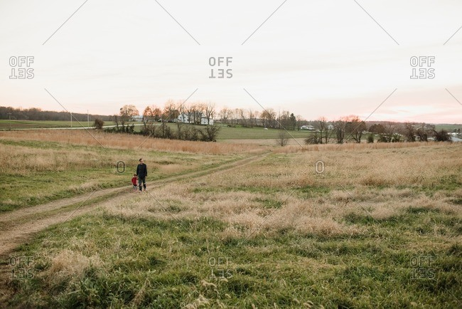 Father and daughter walking together between fields of grass