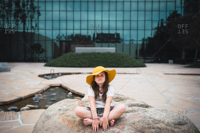Girl in hat sitting on rock in front of office building