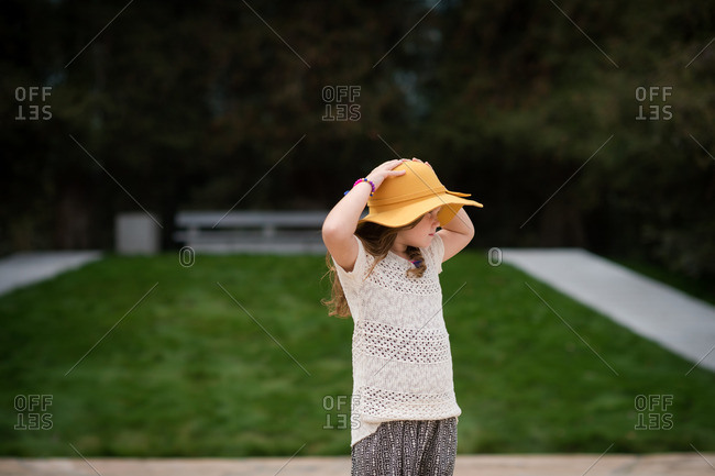 Young girl holding onto her hat in park