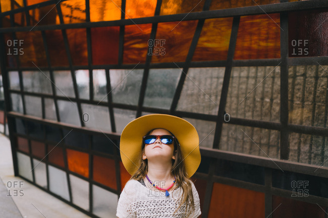 Young girl in hat and sunglasses gazing skyward in front of stained glass wall