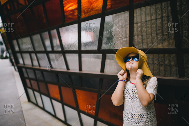 Girl in sunglasses holds onto her hat in front of stained glass wall