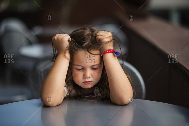 Frustrated young girl with eyes closed gripping her hair at table