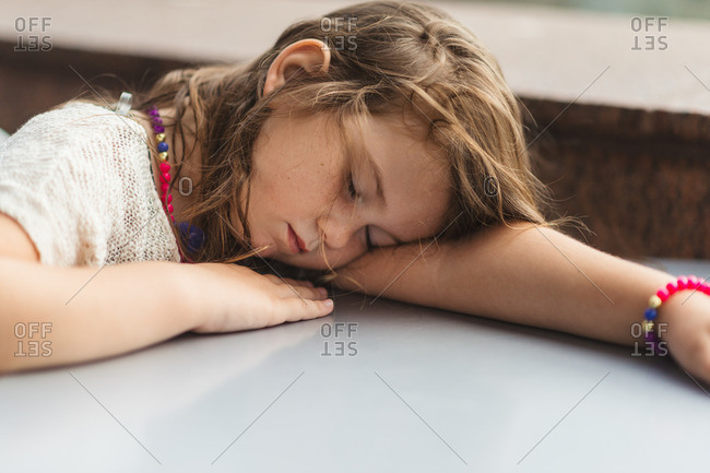 Young girl resting at table