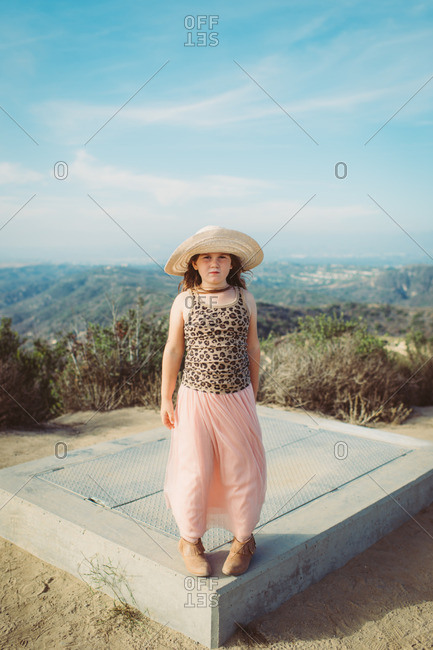 Girl in hat standing at top of hill