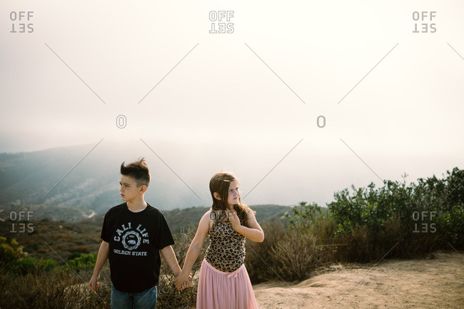Boy and girl hold hands at top of hill
