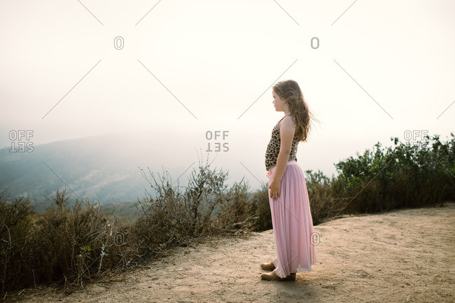 Young girl gazing in distance from hilltop