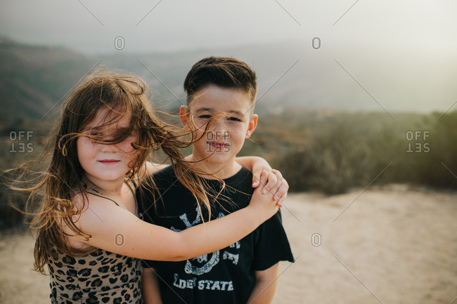 Young girl with arms around her brother