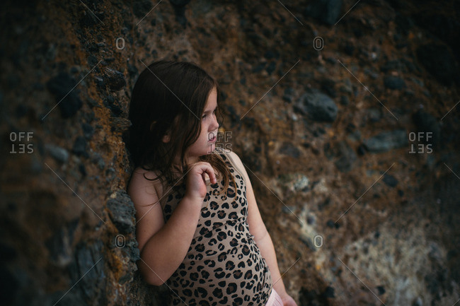 Young girl standing against rock
