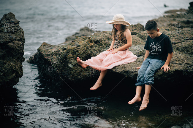 Two young children sitting on rocks by the ocean