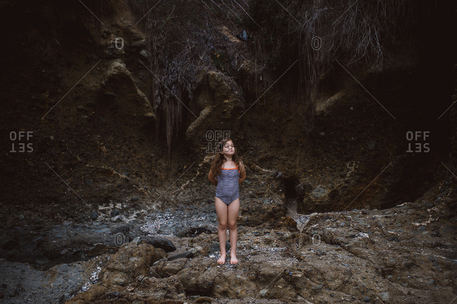 Girl in swimsuit standing proudly by eroded seaside cliff