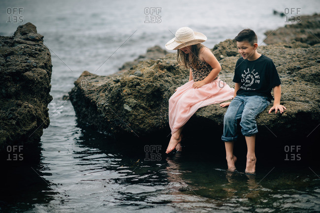 Two young siblings sitting on rocks by the sea