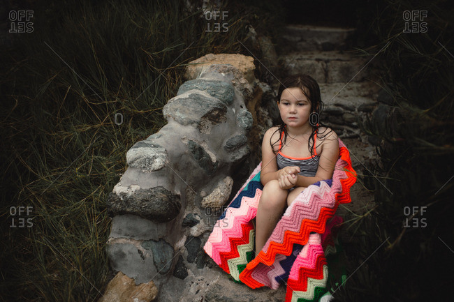 Young girl wrapped in afghan sits on stone stairs in bathing suit