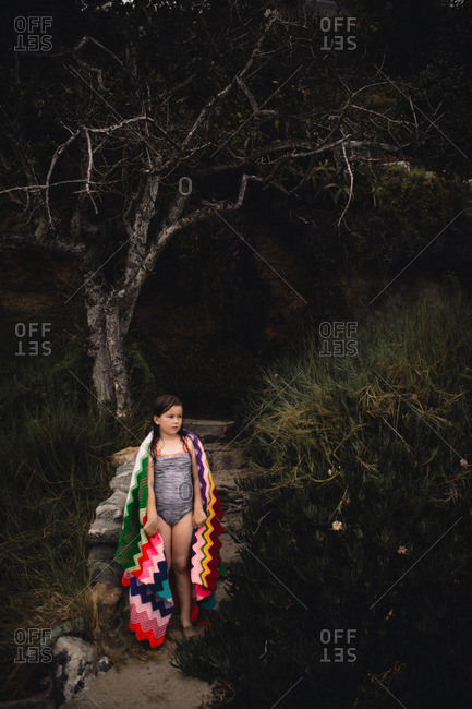 Girl in bathing suit and knitted blanket explores wooded landscape