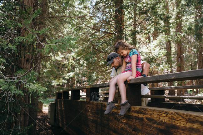 Girl sitting on bridge railing with father