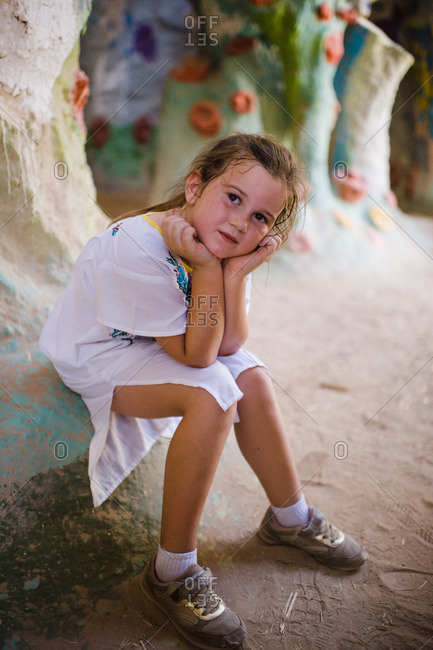 Girl sitting on edge of stucco sculpture