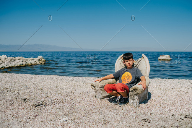 Boy sitting in armchair abandoned on beach