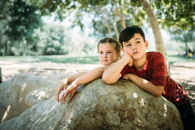 Portrait of siblings leaning on rock