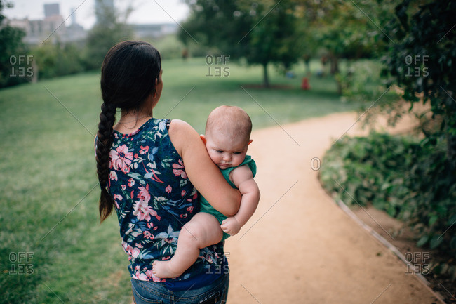 Woman carrying chubby baby on path in park