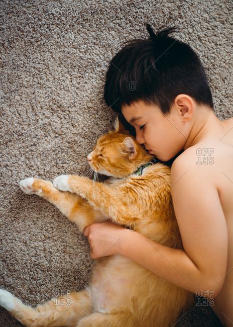 Boy sleeping on rug with orange cat