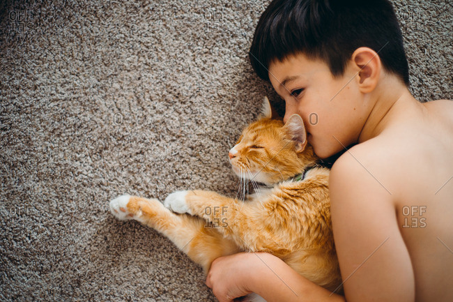 Young boy snuggling on floor with his pet cat
