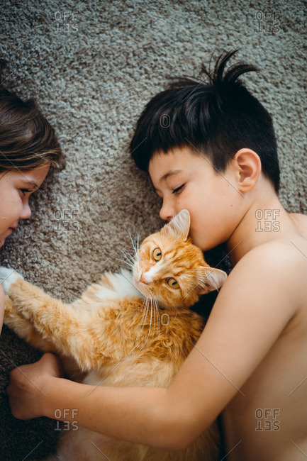 Two young children laying on floor with cat