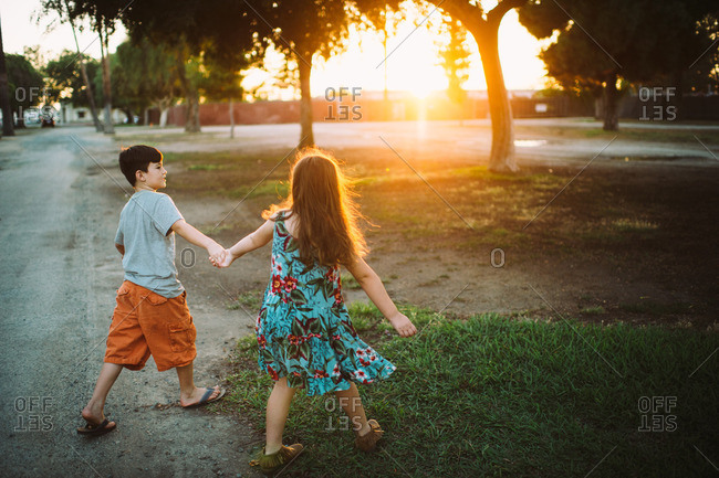 Boy and girl walk hand-in-hand in park at sunset