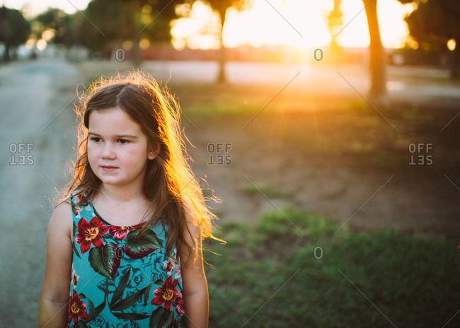 Young girl in flowered dress outdoors at sunset
